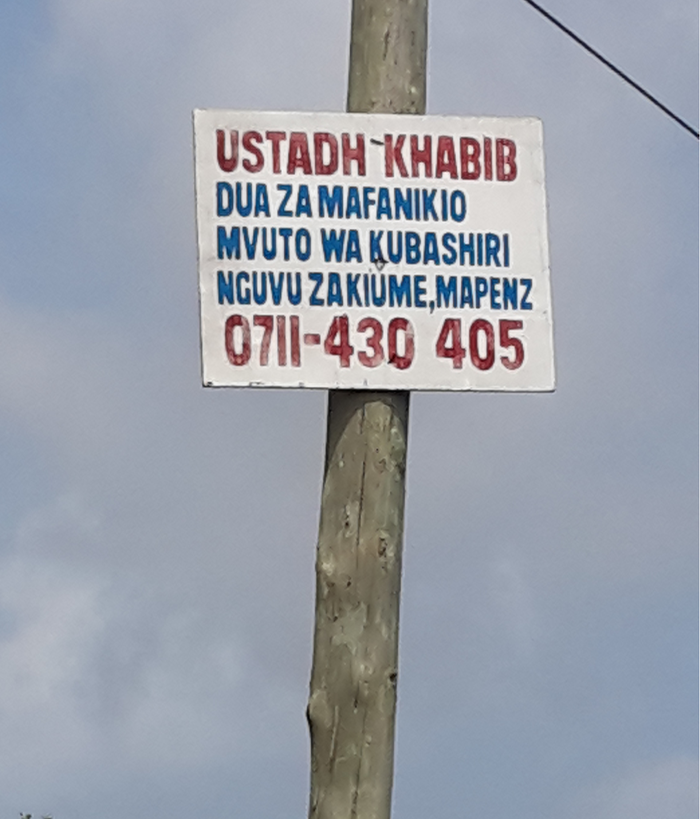 An advertisment posted on a wooden electical pole for a healer who is concerned with sexual  performance (nguvu za kiume) among others.